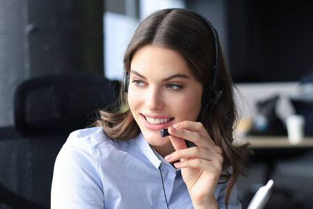 Beautiful smiling call center worker in headphones is working at modern office.