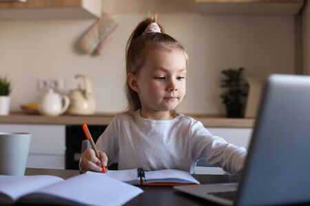 Serious little girl handwrite study online using laptop at home, cute happy small child take Internet web lesson or class on computer, homeschooling concept