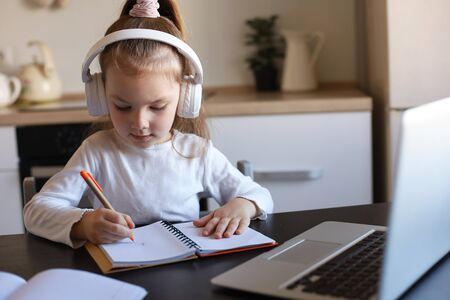 Little girl in headphones sit at desk writing in notebook studying online do exercises at home, little child handwrite prepare homework on quarantine, have web class or lesson indoors