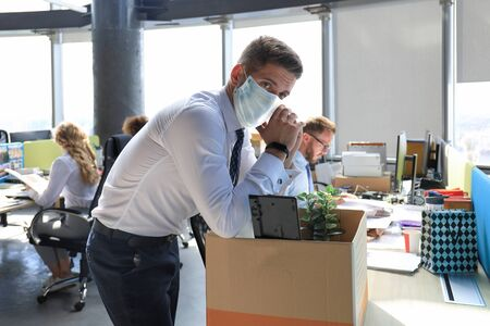 Dismissal employee in preventive medical mask in an epidemic coronavirus. Sad dismissed worker are taking his office supplies with him from office
