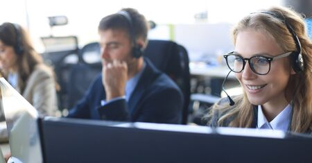 Female customer support operator with headset and smiling, with collegues at background