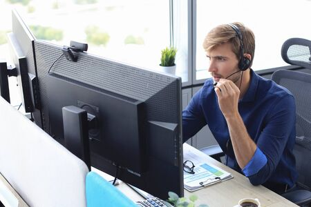 Heureux jeune cadre de support client masculin travaillant au bureau