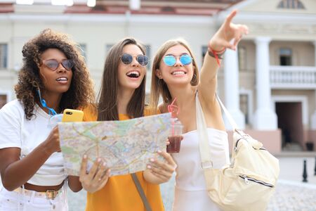 Holidays and tourism concept - beautiful girls looking for direction in the city
