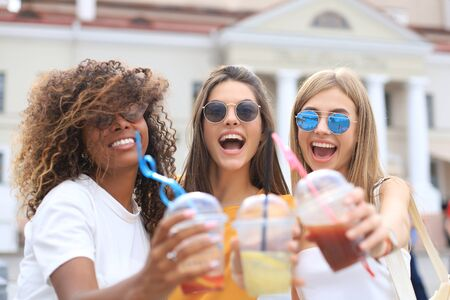 Three trendy cool hipster girls, friends drink cocktail in urban city background