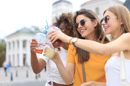 Three trendy cool hipster girls, friends drink cocktail in urban city background Stock fotó