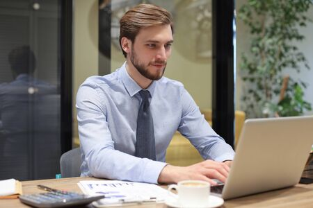 Young modern business man working using laptop while sitting in the office