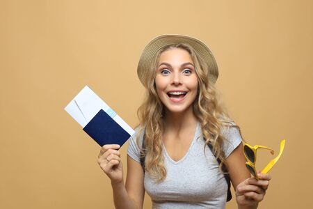 Beautiful blonde woman with sunglasses posing with passport with tickets over beige background 版權商用圖片