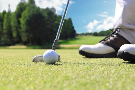 Golf player at the putting green hitting ball into a hole Reklamní fotografie