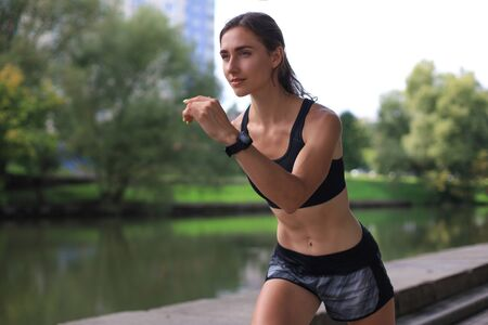 Young woman in sports clothing running while exercising outdoors Stok Fotoğraf