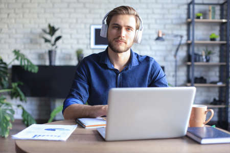 Confident man wearing headset speaking and watching business webinar training, listening to lecture