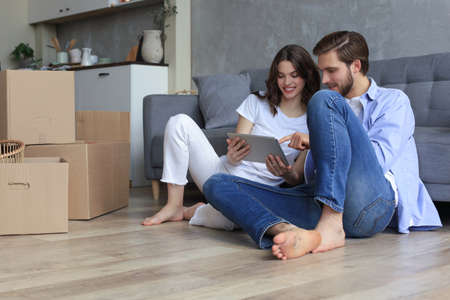 Happy couple sitting and planning new home decoration at home with a tablet at moving day, renovation and interior design for new house.