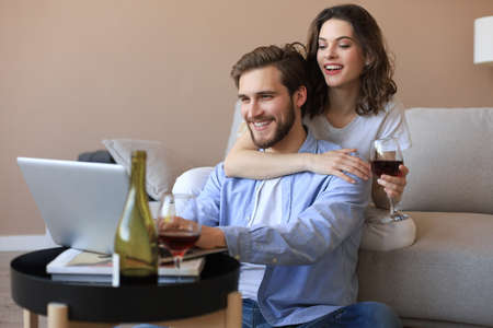 Happy couple sitting, relaxing on floor in living room, using laptop for online shopping together, watching movie