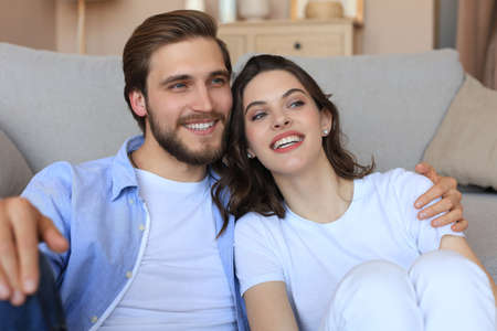 Young loving couple relaxing on floor near sofa together. Woman and man embrace enjoy company of each other sitting on couch holding hands having romantic date