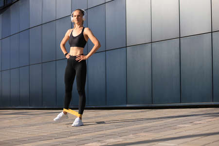Athletic woman doing fitness exercise using fitness gum Stock Photo