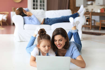Happy mom and little child girl looking at screen laptop, talking to webcam, chatting online via computer app Archivio Fotografico