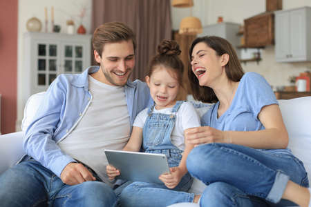 Positive friendly young parents with smiling little daughter sitting on sofa answering togetherering video call on digital tablet while relaxing at home on weekend