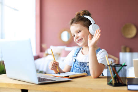 Distance learning. Cheerful little girl girl in headphones using laptop studying through online e-learning system
