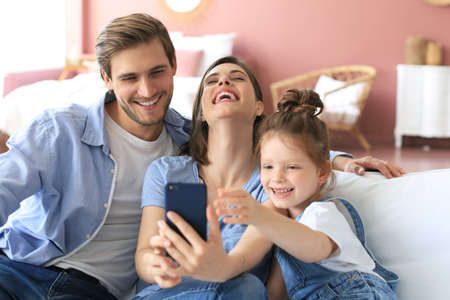 Beautiful young family with little child taking a selfie with a smartphone at home on the couch Foto de archivo