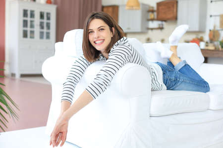 Smiling beautiful woman lying on a sofa in living room at home