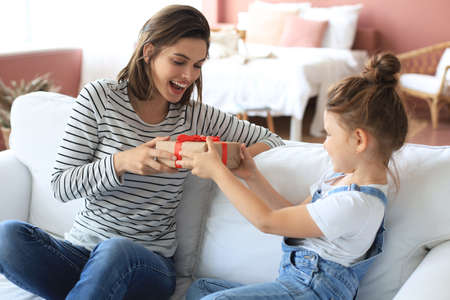 Little girl make birthday present to excited parent while they sitting on couch with mom, smiling little child congratulate give gift box to happy mother Stockfoto