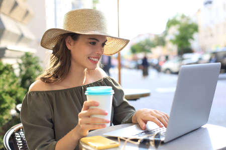 Happy nice woman working on laptop in street cafe, holding paper cup