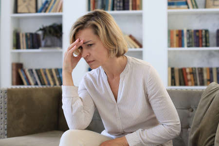 Worried middle aged woman sitting on a sofa in the living room