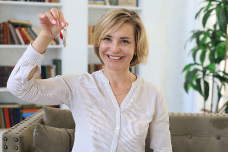 Cheerful middle aged female, real estate agent, sitting on couch, holding keys to new house Imagens