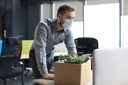Dismissal employee in an epidemic coronavirus covid-19. Sad dismissed worker are taking his office supplies with him from office Stock Photo