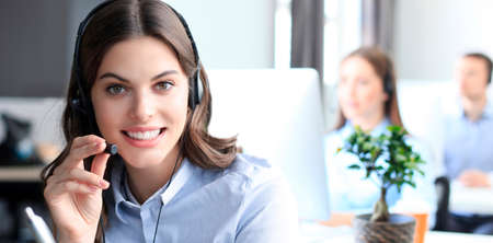 Portrait of call center worker accompanied by his team. Smiling customer support operator at work. Standard-Bild
