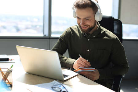 Smiling young business man having video call in office