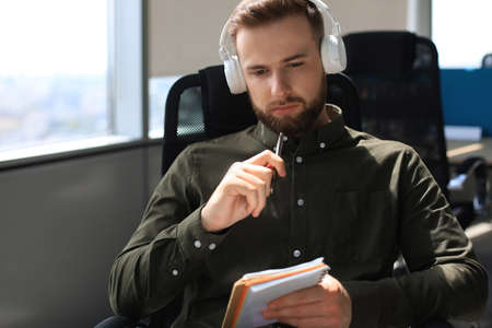 Thoughtful young business man writing something down while working in modern office