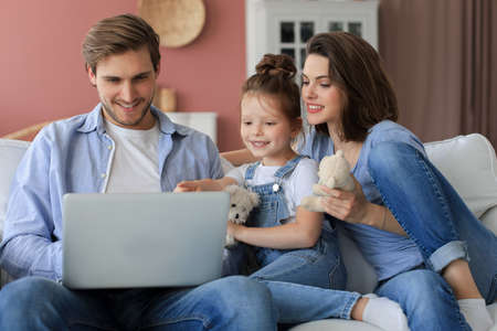 Positive friendly young parents with smiling little daughter sitting on sofa answering togetherering video call on laptop and waving hand in greeting while relaxing at home on weekend Stock Photo