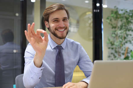 Smiling young business man showing sign OK sitting in the office desk