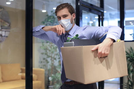 Dismissal employee in preventive medical mask in an epidemic coronavirus. Dismissed worker going from the office with his office supplies