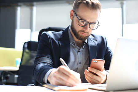 Businessman using his mobile phone in the office