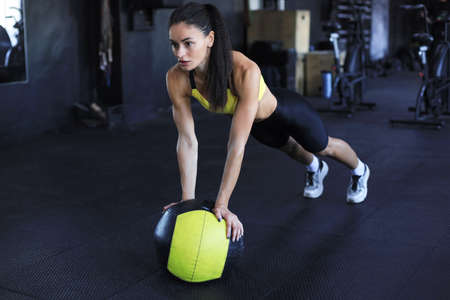 Muscular woman is working out with medicine ball in gym Standard-Bild