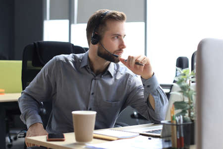Smiling male call-center operator with headphones sitting at modern office, consulting online information in a laptop, looking up information in a file in order to be of assistance to the client