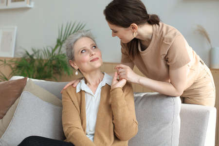 Happy daughter hugging older mother, standing behind sofa in living room, enjoying tender moment at home Stock Photo