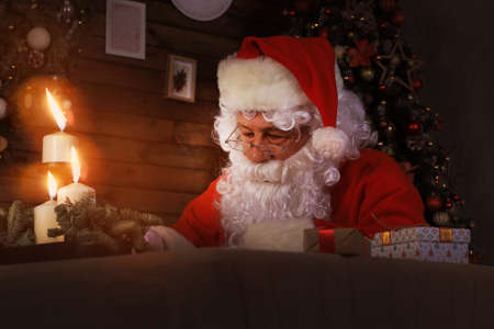 Portrait of happy Santa Claus sitting at his room at home near Christmas tree and answering Christmas letters Stock Photo