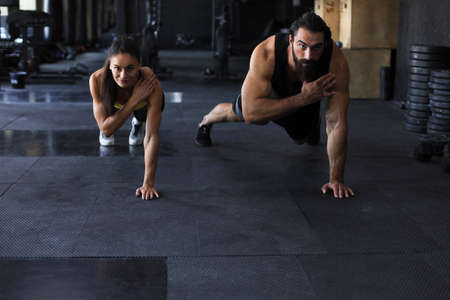 Portrait of beautiful young sports couple on a plank position
