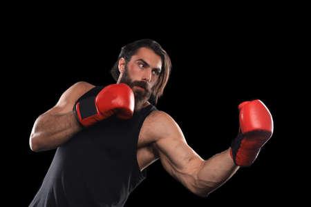 Kickboxer man fighting against black background. Sport concept Stock Photo