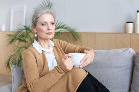 Happy mature woman resting on comfortable sofa drink coffee or tea, looking away, relaxing on cozy couch at home enjoy hot beverage