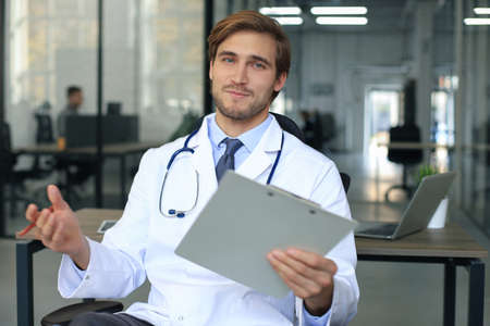 Smiling handsome male doctor talking at camera with patient Stock Photo
