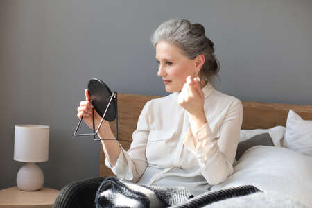 mature woman looking at mirror and touching face at home Foto de archivo