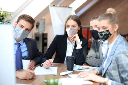 Group of young business people working, communicating while sitting at the office desk together with colleagues in preventive masks during epidemy. Standard-Bild