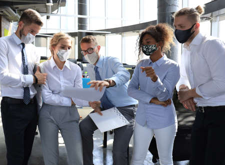 Business team in protective masks works in the office.