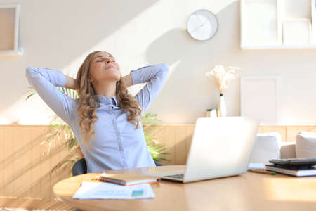 Young woman crossed hands behind head, enjoying break time at home. Peaceful carefree business woman resting at table with computer, looking aside, dreaming of future