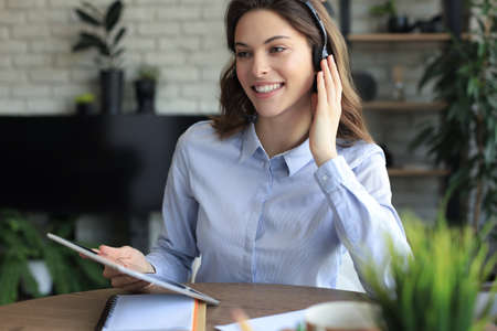 Freelance operator talking with headsets and consulting clients from home office Foto de archivo
