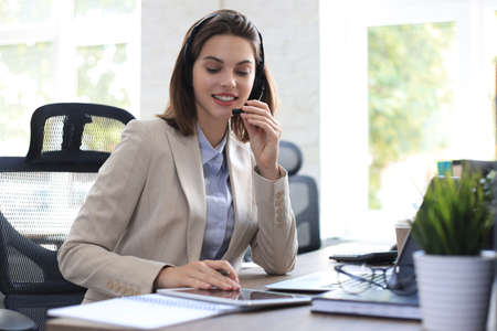 Freelance operator talking with headsets and consulting clients from office