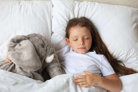 Cute child little girl sleeps in the bed with a toy elephant